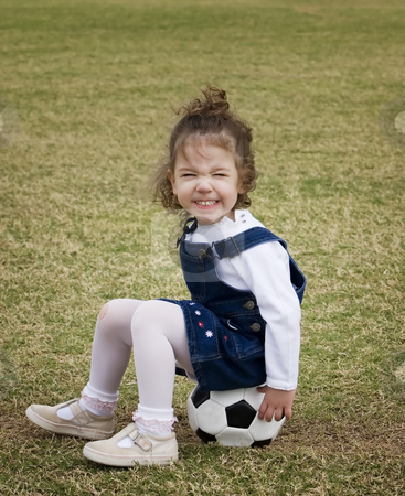Little girl sitting on a soccer ball. stock photo, Little girl on a playground sitting on a soccer ball and making a funny face. by Scott Griessel