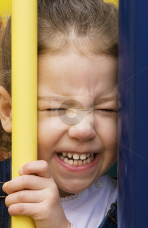 Little girl with a scrunched face stock photo, Little girl on play equipment scrinches her face between two bars. by Scott Griessel