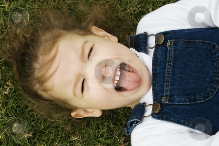 Little Girl in the Grass stock photo, Little girl laying in the grass sticks out her tongue. by Scott Griessel