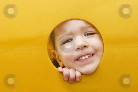 Little girls face through a hole in play equipment stock photo, A little girl sticks her face through a hole in a yellow plastic piece of playground equipment by Scott Griessel