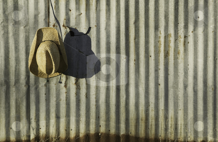 Cowboy hat against corrugated metal. stock photo, Straw cowboy hat hanging in front of old corrugated metal. by Scott Griessel