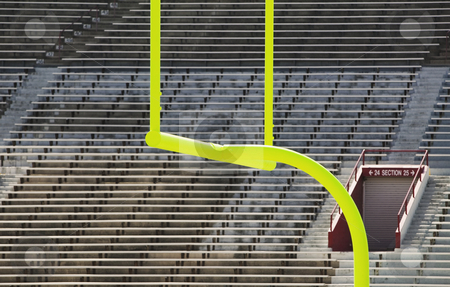 Goal Posts and Empty Stands stock photo, Green goal posts in front of deserted stadium seats. by Scott Griessel