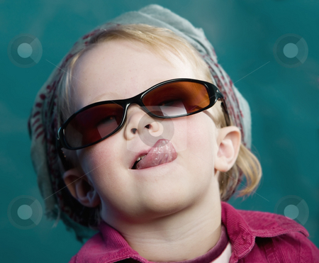 Little girl sticking out her tongue stock photo, Little girl with sunglasses and a scarf sticking out her tongue by Scott Griessel