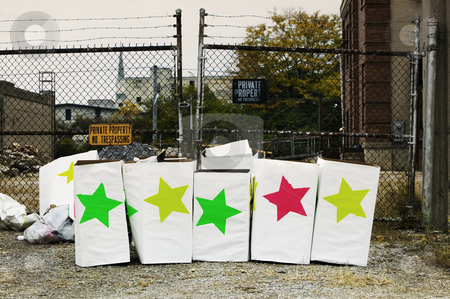 Star Boxes stock photo, Trash boxes with brightly colored stars in front of a chain link fence. by Scott Griessel