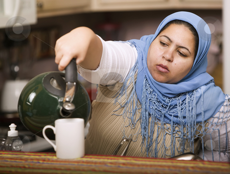 Muslim woman pouring tea stock photo, Muslim woman wearing a head scarf in a western kitchen pouring tea by Scott Griessel