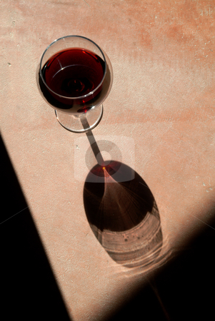 Wine Glass with Dramatic Shadow stock photo, Wine glass with heavy side-light and long by Scott Griessel
