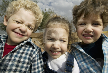 Three Siblings stock photo, Triplets make faces in a wide angle portrait by Scott Griessel