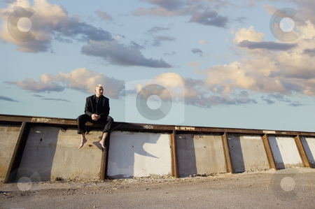 Punk Businessman on a Wall  stock photo, Barefoot businessman with a punk haircut sitting on a wall. by Scott Griessel