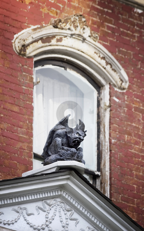 Gargoyle on on Old House stock photo, Gargoyle perched in front of a window on a dilapidated brick house. by Scott Griessel