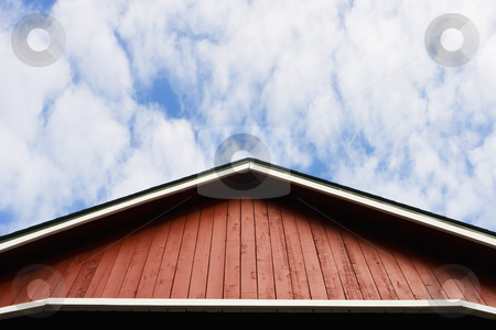Red Roof and Sky stock photo, Red barn-style roof against a sky with soft clouds. by Scott Griessel