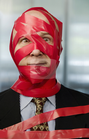 Red Tape stock photo, Businessman wrapped in red tape by Scott Griessel