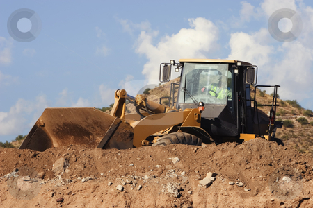 Construction Vehicle stock photo, Construction vehicle moving dirt on top of a hill. by Scott Griessel