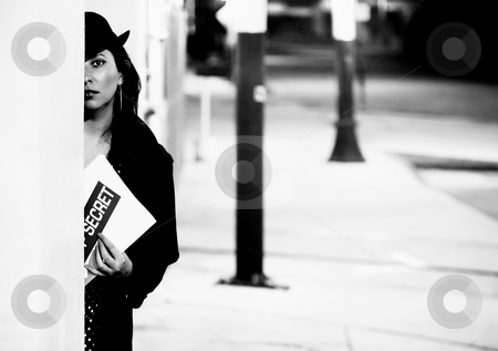 Woman Spy with Document stock photo, Woman spy hiding and holding a top seceret document. by Scott Griessel