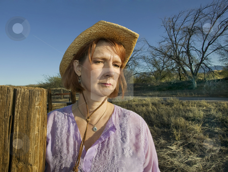Ranch Woman stock photo, Portrait of a woman in a purple shirt and cowboy hat on a ranch. by Scott Griessel