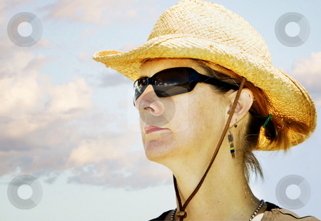 Woman in a Cowboy Hat stock photo, Woman in bright sun wearing a cowboy hat looks off to the side. by Scott Griessel