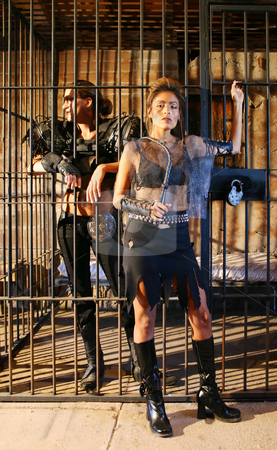 Jailer and Captive. stock photo, Futuristic woman jailer guards a woman prisoner. by Scott Griessel