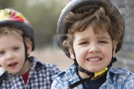 Little boys in a bicycle helmets stock photo, Two little boys in bicycle helmets - one boy looks concerned by Scott Griessel