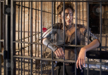 Tough Woman in Jail stock photo, Tough science-fiction woman behind bars in a retro jail. by Scott Griessel