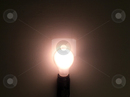 Lit Bulb stock photo, A bulb is lit and surrounded by the darkness by Rebecca Mosoetsa