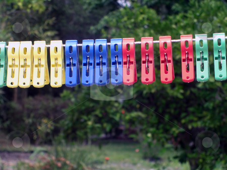 Colorful Pegs stock photo, A line of colorful pegs are on the line by Rebecca Mosoetsa