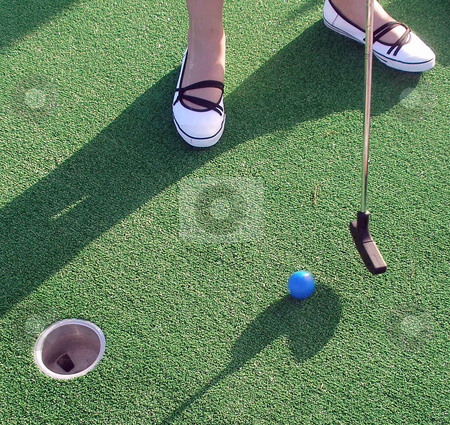Adventure Golf stock photo, Playing Adventure Golf, feet, club, ball and hole. by Lucy Clark
