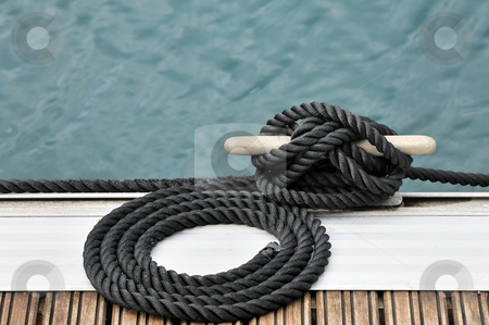 Rope and bitt stock photo, Black rope tied up on a bitt securing boat to jetty by Massimiliano Leban