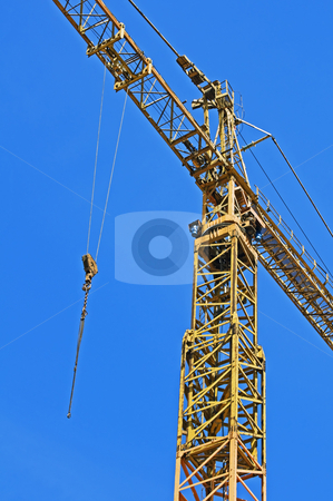Crane stock photo, Detail of a yellow crane with hook against a blue sky by Massimiliano Leban