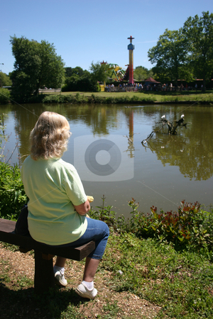 Theme Park View stock photo, Carole sitting on a bench looking over the look at a theme park in the UK. by Lucy Clark