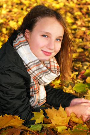 Girl in a fall park stock photo, Portrait of a beautiful teenage girl in a fall park with fallen leaves by Elena Elisseeva