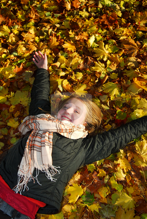 Girl in a fall park stock photo, Beautiful teenage girl lying on fallen leaves in autumn park by Elena Elisseeva