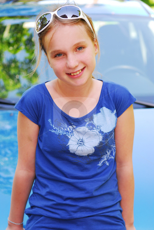 Girl portrait stock photo, Portrait of a young girl in sunglasses sitting on a car hood by Elena Elisseeva