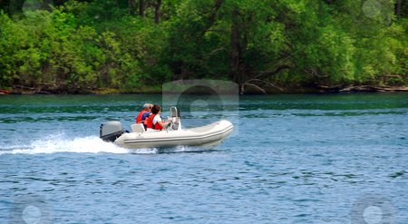 Boating on river stock photo, A couple driving an inflatable boat on a river by Elena Elisseeva