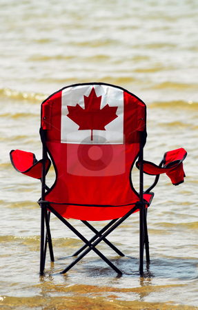 Canadian vacation stock photo, Folding chair with canadian flag design in shallow lake water, canadian vacation concept by Elena Elisseeva