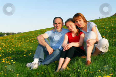 Family portrait stock photo, Portrait of a happy family of three on blooming summermedow by Elena Elisseeva