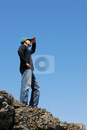Man looking stock photo, A man standing on top of a cliff looking into the distance by Elena Elisseeva