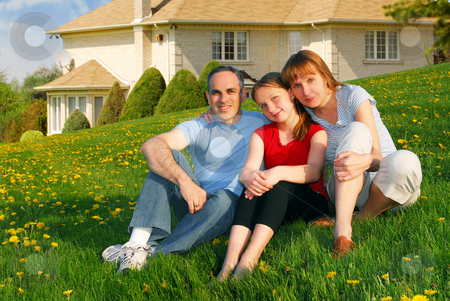Family at a house stock photo, Portrait of a happy family of three on the lawn on front of their house by Elena Elisseeva