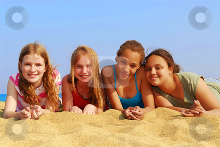 Girls on beach stock photo, Portrait of four smiling teenage girls on a sandy beach by Elena Elisseeva
