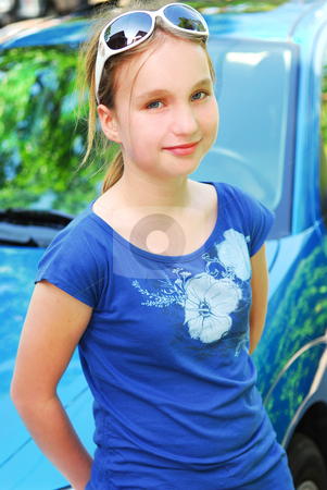 Smiling girl stock photo, Portrait of a smiling young girl leaning on car hood by Elena Elisseeva