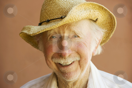 Senior Citizen Man in a Cowboy Hat stock photo, Senior Citizen Man Smiling in a Straw Cowboy Hat by Scott Griessel