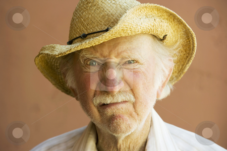 Senior Citizen Man in a Cowboy Hat stock photo, Senior Citizen Man Frowning n a Straw Cowboy Hat by Scott Griessel