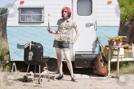 Girl in front of a trailer stock photo, Girl in front of a trailer with a hotdog and a barbecue by Scott Griessel