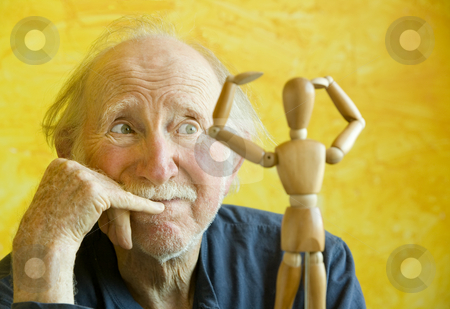 Artist Ponders a Wooden Model stock photo, Elderly Artist Ponders a Wooden Figure Model by Scott Griessel