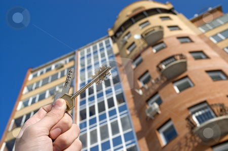 Modern Condominium. stock photo, On a background of a modern brick house, hand with keys from an apartment. by Yury Ponomarev