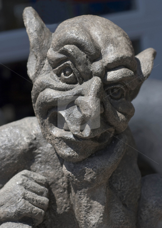 Gargoyle stock photo, A statue of a gargoyle shown from the shoulders up. He has his hand under his chin like he is thinking about something by Maria Bell
