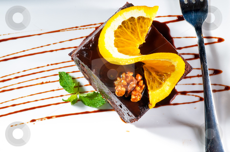 Chocolate and walnuts cake stock photo, fresh baked delicious chocolate and walnuts cake with slice of orance on top and mint leaf by Francesco Perre