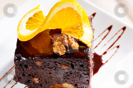 Chocolate and walnuts cake stock photo, fresh baked delicious chocolate and walnuts cake with slice of orance on top by Francesco Perre