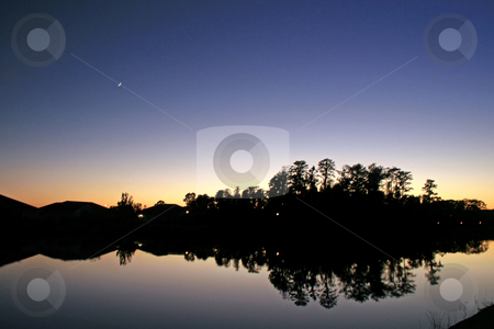 Sunset Reflections stock photo, A Sunset, Moon, Trees, Lake and Silhouettes by Lucy Clark