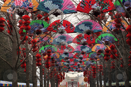Paper Fans Lucky Red Lanterns Chinese Lunar New Year Decorations stock photo, Paper Fans Lucky Red Lanterns Chinese New Year Decorations Stone Gate Ditan Park Beijing China.  During Lunar New Year, many parks and temples in China have large outdoor fairs, festivals.  Chinese characters on lanterns say lucky and long life. by William Perry