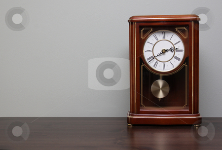 Clock on a Table stock photo, A classic analog clock sitting a table with copy-space.  by Chris Hill