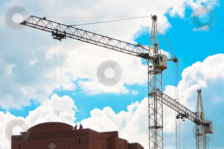 Tower cranes on the construction site stock photo, Tower cranes on the construction site against a background of the sky by Megaloman1ac